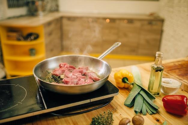 Carne assada em uma frigideira no fogão elétrico