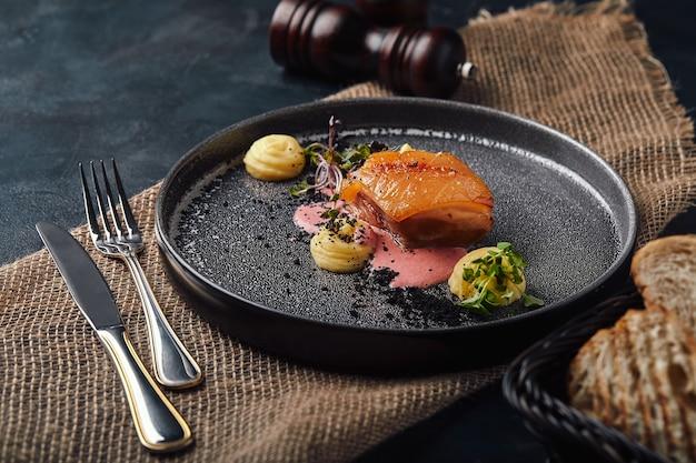 Carne assada lindamente enlatada em pratos, servida na panela do chef, com purê de batata e molho de brócolis de beterraba. foto de comida, estilo rústico.