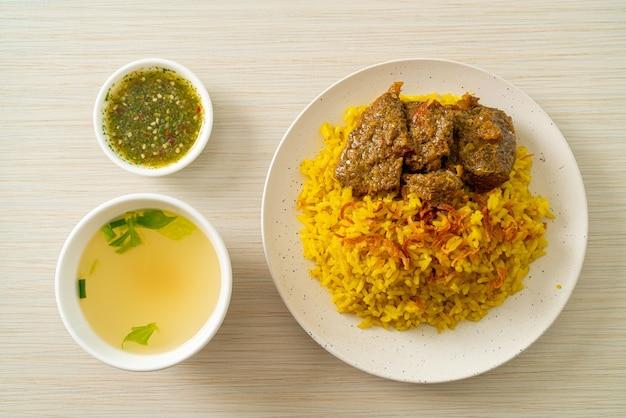 Carne biryani ou arroz com caril e carne. versão tailandesa-muçulmana do biryani indiano, com aromático arroz amarelo e carne bovina. comida muçulmana