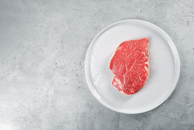 Carne bovina em um prato branco, vista superior com espaço de cópia
