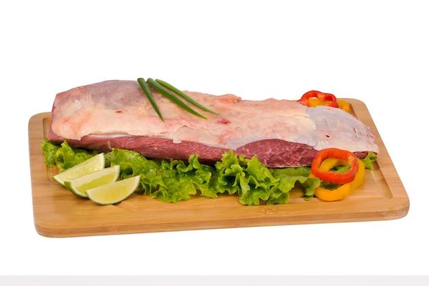 Carne bovina fresca e crua na tábua em fundo branco.
