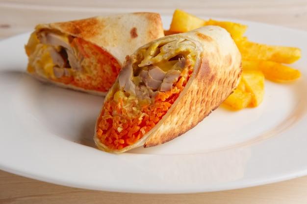 Carne, cenoura apimentada, repolho e queijo enrolados em pão pitta fino