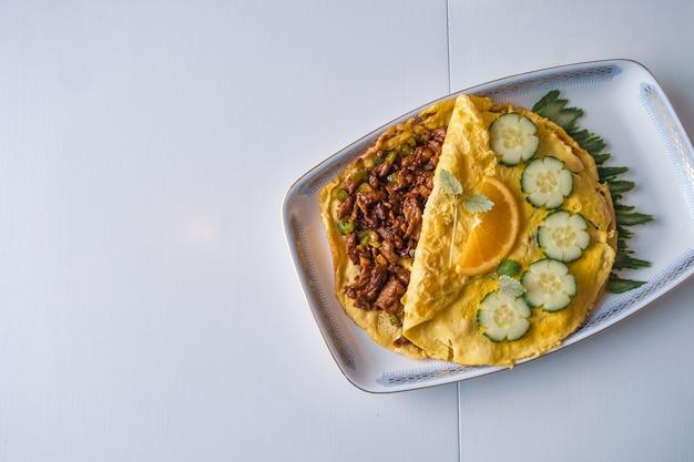 Carne cheia de omelete frito com legumes na mesa branca
