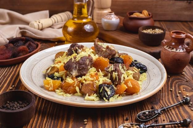 Carne com arroz frutas secas ameixas castanhas especiarias óleo vista lateral