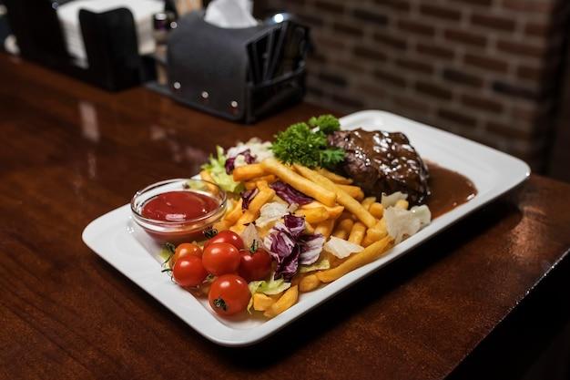 Carne com batata frita e tomate