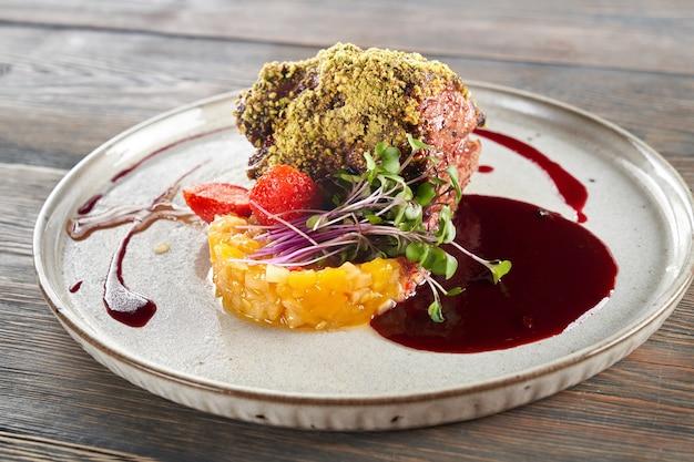Carne com cobertura de pistache servida com frutas e frutas vermelhas