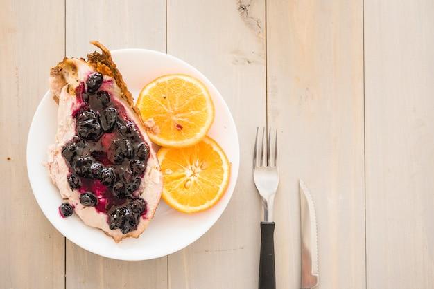 Carne com geléia perto de laranjas no prato