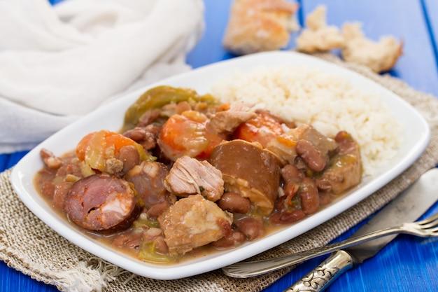 Carne com legumes e salsichas no prato