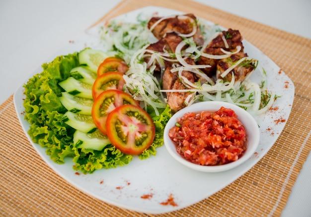 Carne com legumes em um prato branco.