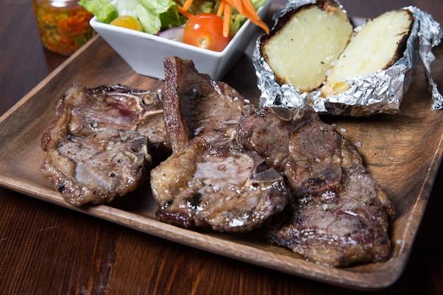Carne com legumes em uma placa de madeira