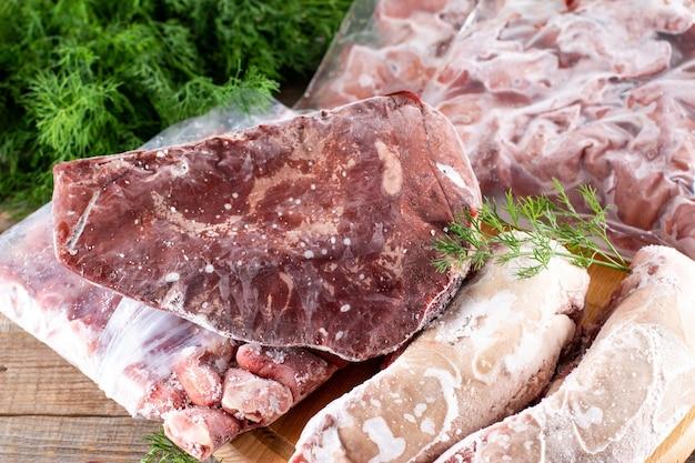 Carne congelada. miudezas congeladas, fígado, coração, estômagos em um saco plástico sobre uma mesa de madeira. produtos congelados. alimentos congelados