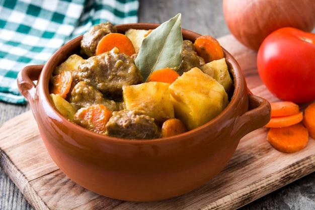 Carne cozida com batatas, cenouras e especiarias em uma tigela na mesa de madeira