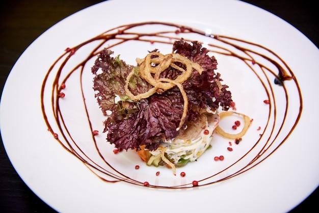 Carne cozida com legumes e molho em um prato branco sobre um fundo escuro.
