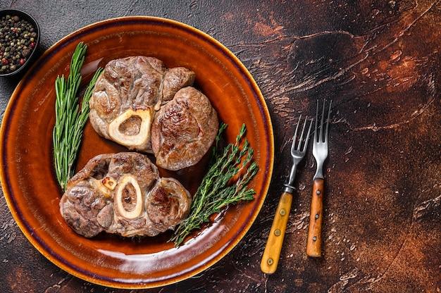 Carne cozida com osso pernil de vitela osso buco, bife italiano ossobuco. fundo de madeira escuro. vista do topo. copie o espaço.