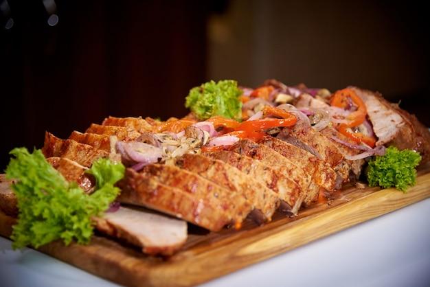 Carne cozida cortada com molho em uma placa de madeira.