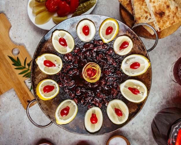 Carne cozida em um saj em suco de romã e fatias de limão fatiadas