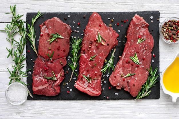 Carne crua, bife com especiarias, azeite e alecrim na tábua de ardósia preta sobre a mesa de madeira