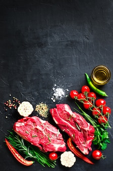 Carne crua, bife de carne em uma tábua de pedra com alecrim, especiarias, sal, azeite, tomate cereja
