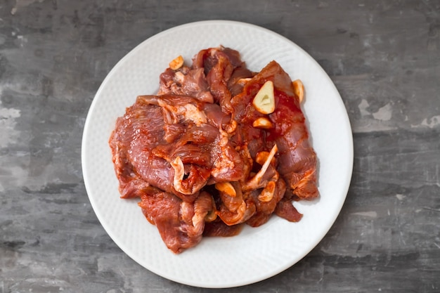 Carne crua com ervas e alho para grelhar no prato