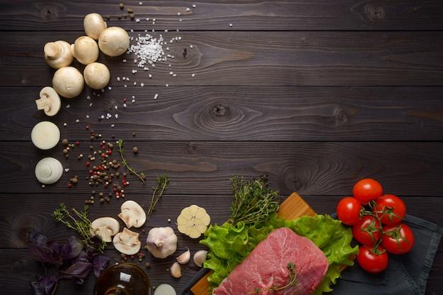 Carne crua com ingredientes em um fundo de madeira