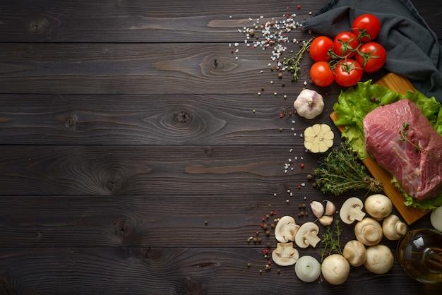 Carne crua com ingredientes em uma mesa de madeira