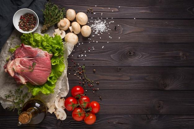 Carne crua com ingredientes numa superfície de madeira