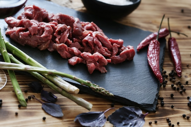 Carne crua com ingredientes para cozinhar a refeição