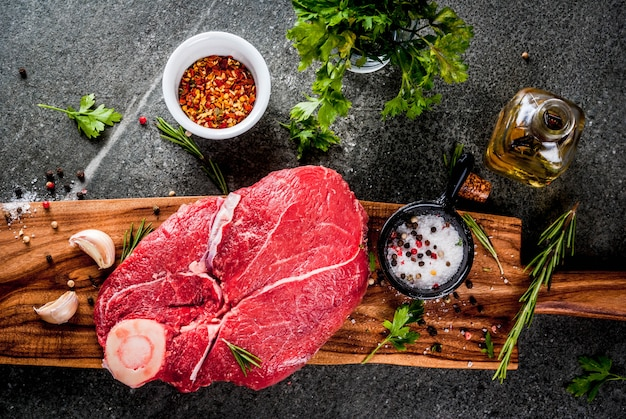 Carne crua com ingredientes para cozinhar. filé de carne, lombo com osso, sobre uma tábua, com sal, pimenta, salsa, alecrim, azeite, alho, especiarias. em uma mesa de pedra preta, copie a vista superior do espaço