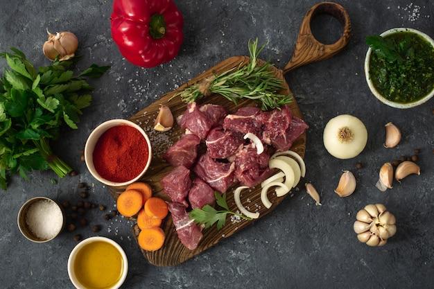 Carne crua com ingredientes para cozinhar