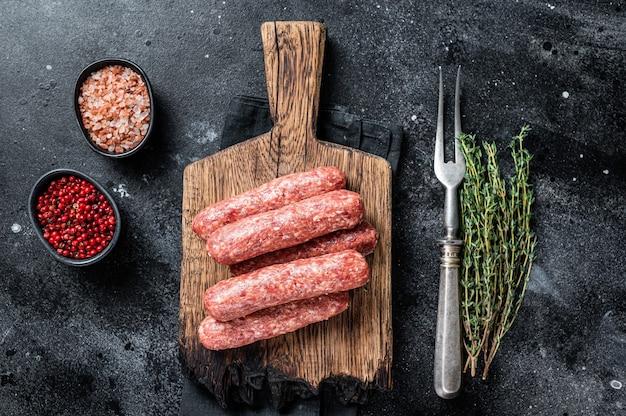 Carne crua crua e salsichas de carne de cordeiro em uma placa de madeira. fundo preto. vista do topo.