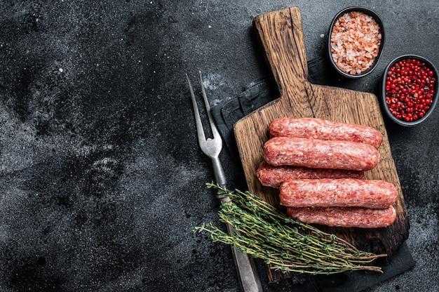 Carne crua crua e salsichas espetadas de carne de cordeiro em uma placa de madeira. fundo preto. vista do topo. copie o espaço.
