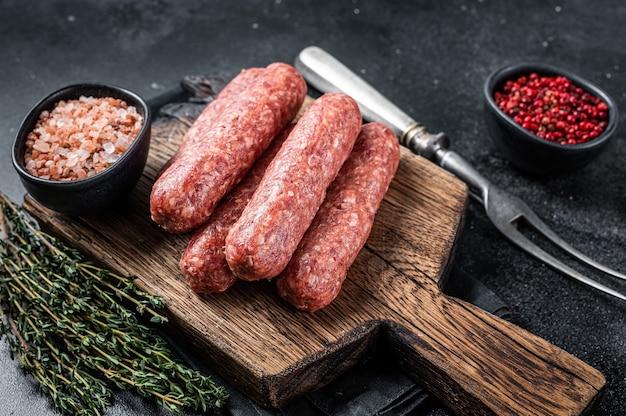 Carne crua crua e salsichas espetadas de carne de cordeiro em uma placa de madeira. fundo preto. vista do topo.