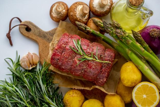 Carne crua de carne vermelha com alecrim verde e legumes frescos em uma tábua de madeira