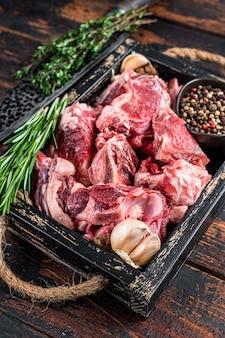 Carne crua de cordeiro ou cabra cortada em cubos para guisado com osso. fundo de madeira escuro. vista do topo.