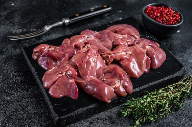 Carne crua de fígado de frango na placa de mármore com tomilho. mesa preta. vista do topo.