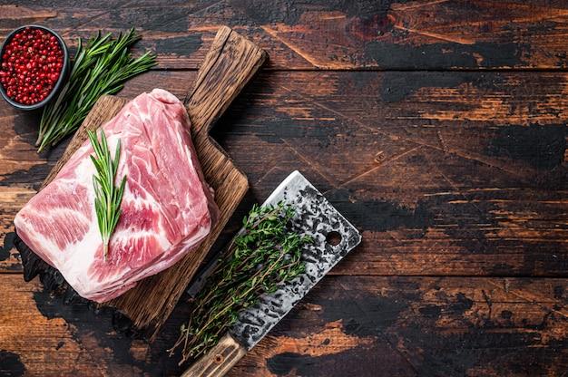 Carne crua de ombro de porco para bifes frescos em uma tábua de madeira com cutelo de açougueiro. madeira escura
