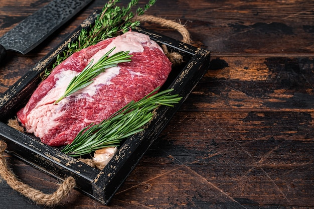 Carne crua de peito cortado em uma bandeja de madeira com uma faca. fundo de madeira escuro. vista do topo. copie o espaço.