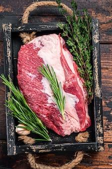 Carne crua de peito cortado em uma bandeja de madeira com uma faca. fundo de madeira escuro. vista do topo.