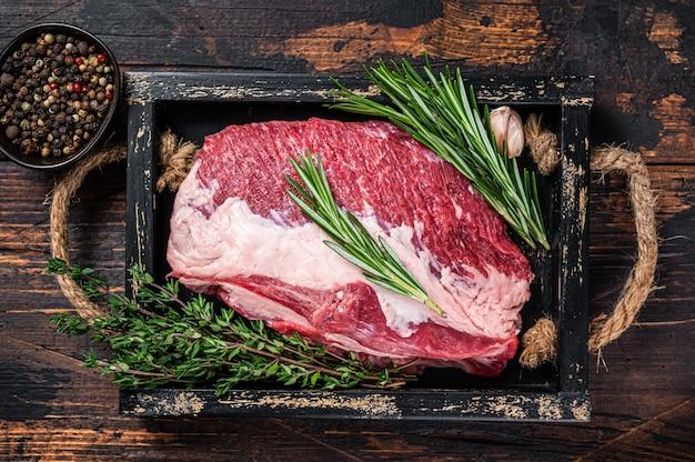 Carne crua de peito de vaca cortada em uma bandeja de madeira com faca
