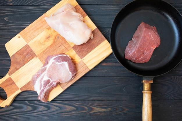 Carne crua diferente na panela de cozimento preto, vista superior. mesa de madeira.