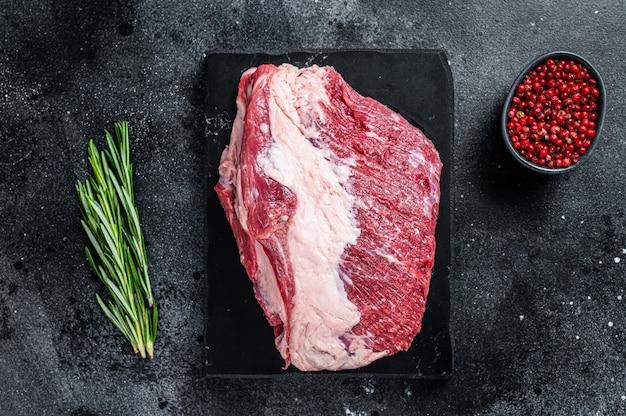 Carne crua do lado de fora de rosbife redondo cortada em uma placa de mármore