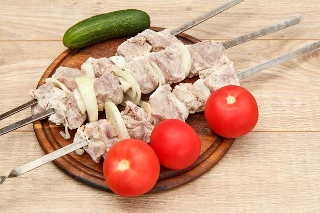 Carne crua e cebola em espetos estão prontas para cozinhar. pepino fresco e tomate, fatias de costeleta de carne na tábua de madeira.