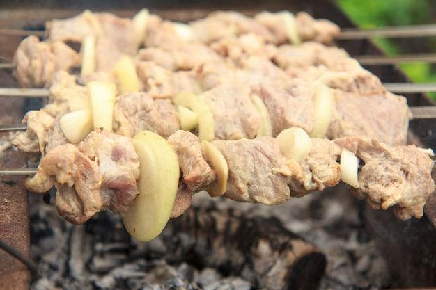 Carne crua e cebolas no espeto são grelhadas no carvão. cozinhar um prato de shish kebab no churrasco. piquenique, comida de rua. foco seletivo