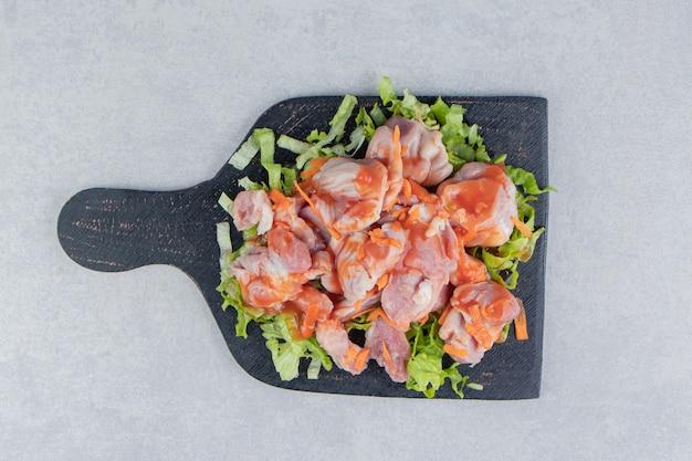 Carne crua e salada no tabuleiro, na superfície branca