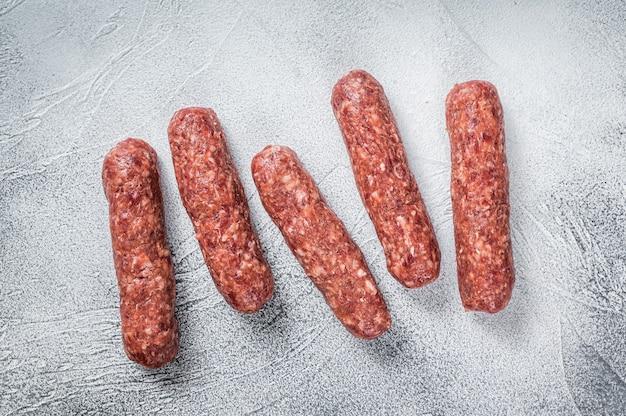 Carne crua e salsichas de espetadas de carne de cordeiro em uma mesa de açougueiro. fundo branco. vista do topo.