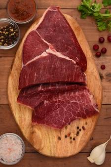 Carne crua em uma placa de corte de madeira pronta para cozinhar em casa. vista do topo. temperos são enquadrados de angus carne com alho