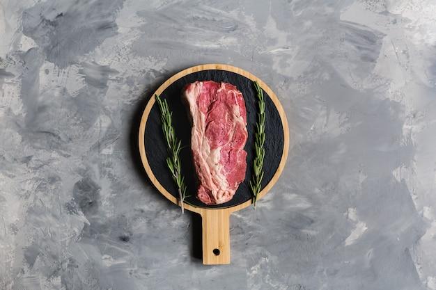 Carne crua em uma tábua com alecrim erva