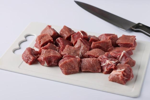 Carne crua fatiada em uma placa de plástico