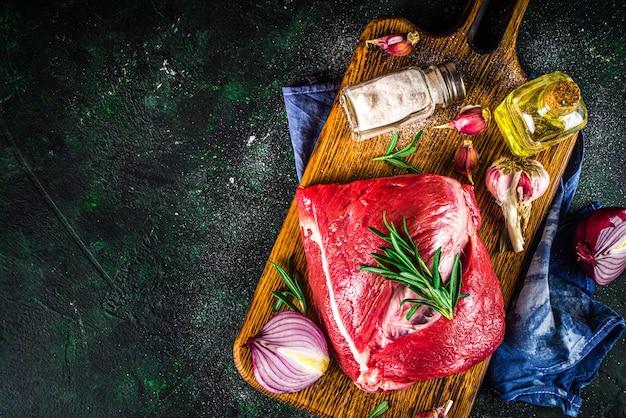 Carne crua, filé de boi, pedaço grande em uma tábua com temperos para cozinhar.