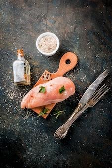 Carne crua, filé de peito de frango, com azeite de oliva, ervas e especiarias no escuro
